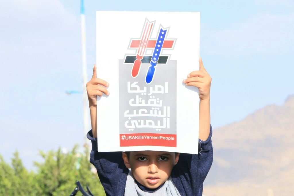 طفل يمني يرفع لافتة احتجاج على مشاركة أمريكا في حرب اليمن